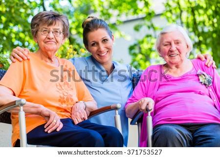 Geriatric nurse having chat with senior women - stock photo