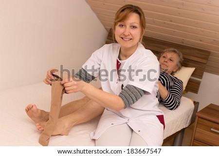 Geriatric nurse helps pensioner during tightening anti-thrombosis stockings - stock photo