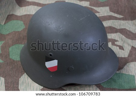 German Army helmet World War II period on camouflaged background - stock photo