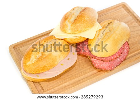 German bread rolls with mortadella, cheese and pepper cervelat on a wooden breakfast tray - stock photo