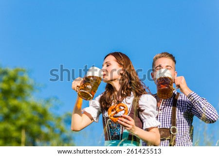 German couple in Tracht with beer and pretzel - stock photo