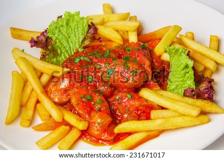 german currywurst. chicken sausage in tomato sauce with curry and fries on white plate - stock photo