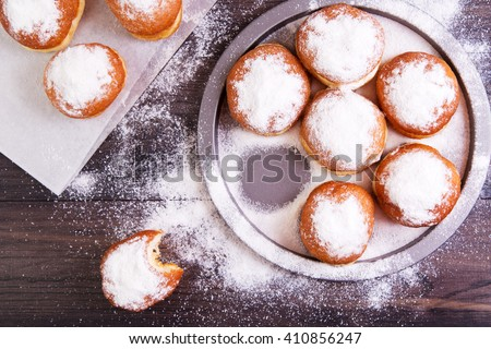 German donuts - berliner with jam and icing sugar in a tray on a dark wooden background. Top view - stock photo