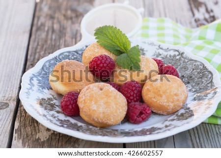 German donuts - krapfen or berliner - filled with jam. On wooden table. Selective focus, natural light. - stock photo
