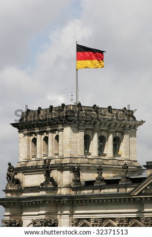 german flag floating above the reichstag, berlin, germany - stock photo
