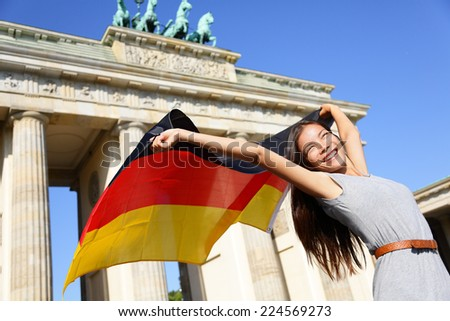 German flag - Woman happy at Berlin Brandenburg Gate cheering celebrating waving flag by Brandenburger Tor, Germany. Cheerful excited multiracial woman in Germany travel concept. - stock photo