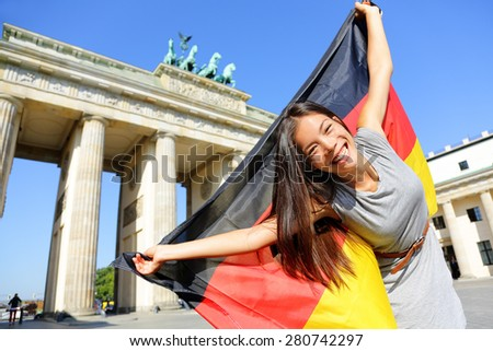 German flag - Woman happy at Berlin, Germany, Brandenburg Gate cheering celebrating waving flag by Brandenburger Tor. Cheerful excited multiracial woman in Germany travel concept. - stock photo
