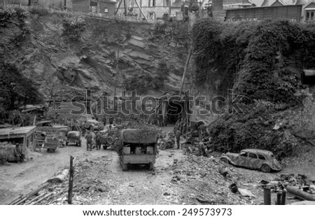 German garrison of Cherbourg surrenders on June 26, 1944. Photo shows U.S. and German soldiers at entrance to the underground quarry that served as the Germans' bunker during the Battle of Cherbourg. - stock photo