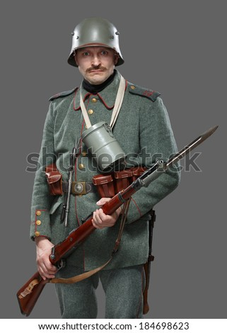 German infantryman during the first world war. Soldier with gun. Isolated on gray. - stock photo