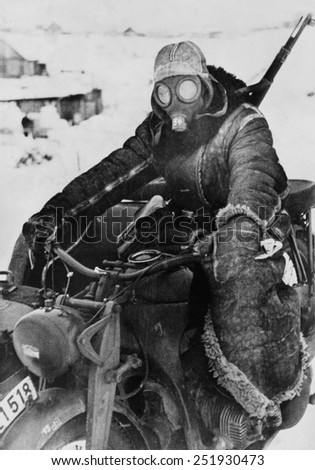 German motorcycle on the Soviet (Russian) Eastern front in the winter of 1942. He wears his gas mask to protect his face from the bitter cold, during World War 2. - stock photo