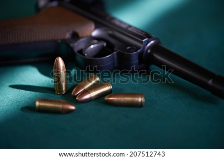 German Parabellum pistol with cartridges on green background - stock photo