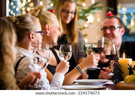 German parents and children toasting with wine and water at Christmas eve dinner  - stock photo