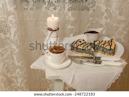 German poppy seed cake on white plate with chocolate and coffee - stock photo