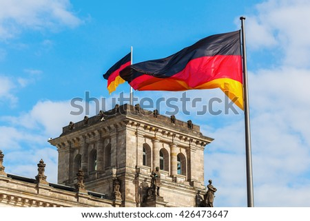 German Reichstag in Berlin, Germany, with national flag - stock photo