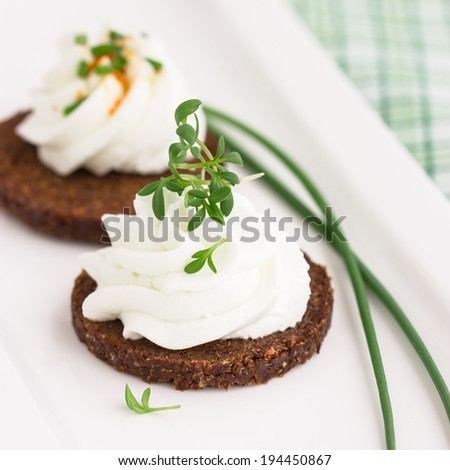 German rye bread pumpernickel with cream cheese, raw vegetables and herbs. Selective focus - stock photo