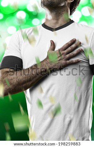 German soccer player, listening to the national anthem with his hand on his chest. On a green lights background. - stock photo