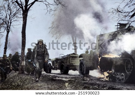 German soldiers passing burning U.S. equipment in the beginning of the Battle of the Bulge. Dec. 16-22, 1944. Still from a captured German film with color added later. B&W Photo with oil color. - stock photo