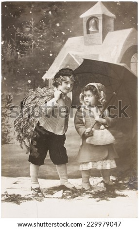 GERMANY, AACHEN - CIRCA 19011 old photo of christmas winter scene with two children carrying evergreen tree. Illustrative Image, subject of human interest - stock photo