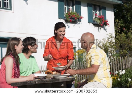 Germany, Bavaria, People eating soup in garden - stock photo