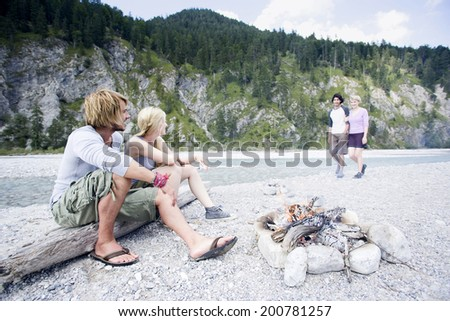 Germany, Bavaria, T\x9Alzer Land, couple sitting at campfire near river other couple approaching - stock photo