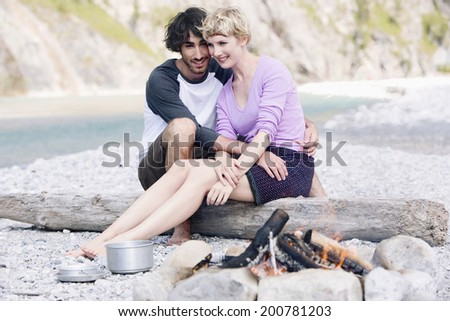 Germany, Bavaria, T\x9Alzer Land young couple sitting at campfire near river embracing - stock photo
