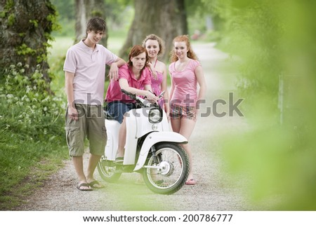 Germany, Bavaria, teenagers standing by moped - stock photo