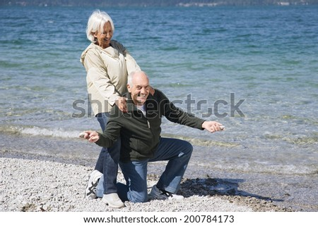 Germany, Bavaria, Walchensee, senior couple fooling about on lake shore man kneeling woman standing behind his back - stock photo