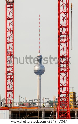 Germany, Berlin - TV Tower seen through two big building cranes.  - stock photo