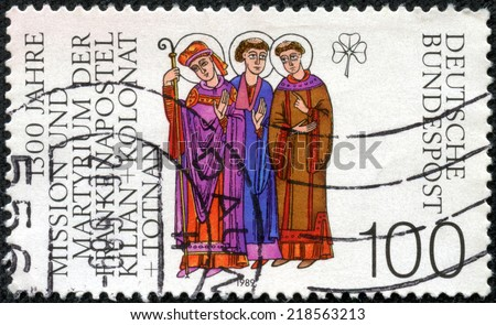 GERMANY - CIRCA 1989: a stamp printed in the Germany shows Saints Kilian, Colman and Totnan, Martyred Missionaries in Germany and clover, circa 1989 - stock photo