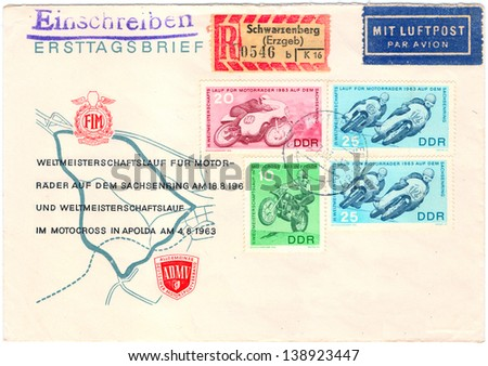 GERMANY - CIRCA 1963: An old used German Democratic Republic envelope and 4 postage stamps issued in honor of the world cup run for motorcycles showing fragments of the competition; series, circa 1963 - stock photo