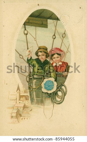 GERMANY - CIRCA 1913: Vintage postcard depicts two children in an air balloon, circa 1913, Germany. A little boy holds an envelope in his raised hand, standing next to his sister - stock photo