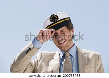Germany Hamburg portrait of man holding sailor cap smiling - stock photo