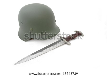 """Germany in the Second World War. Composition with the most widespread battle helmet (M35) and  dagger of assault detachment (Sturmabteilung - SA). Inscription on blade - """"All for Germany"""". - stock photo"""