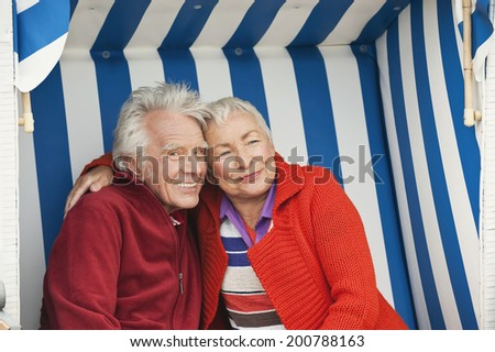Germany North Sea St.Peter-Ording senior couple sitting on hooded beach chair - stock photo