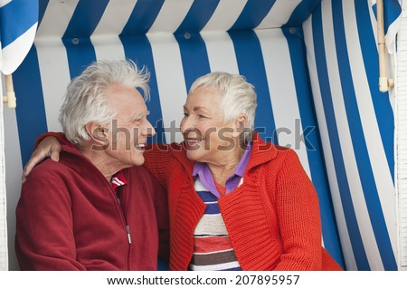 Germany, North Sea, St.Peter-Ording, senior couple sitting on hooded beach chair - stock photo