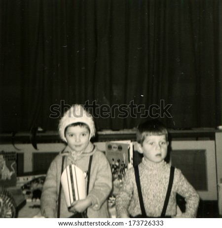 GERMANY - 1960s: An antique photo shows little boy and girl standing in front of the stage - stock photo