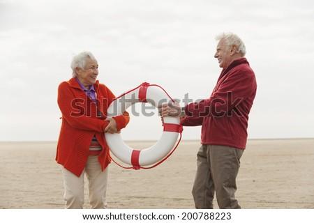 Germany St. Peter-Ording North Sea senior couple holding lifesaver on beach - stock photo