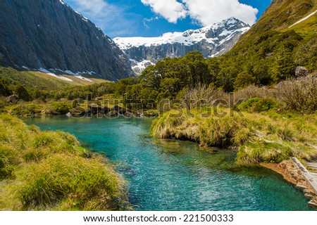 Gertrude Saddle with a snowy mountains and a turquoise lake, Fiordland national park, New Zealand South island - stock photo