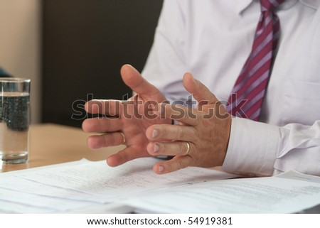Gesticulating hands of a businessman at a meeting - stock photo