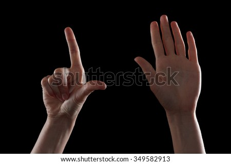 Gesture, a beautiful young woman's hand indicates the direction or making gestures on touch devices. Isolated on black background - stock photo