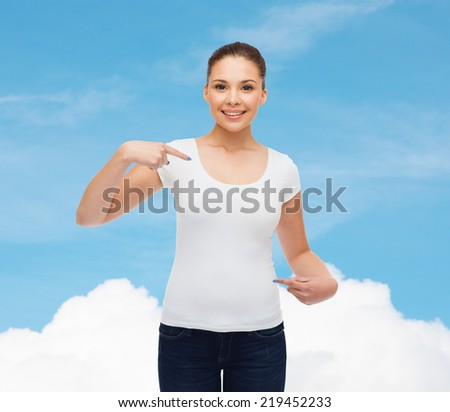 gesture, advertising, dream and people concept - smiling young woman in blank white t-shirt pointing fingers on herself over blue sky background - stock photo