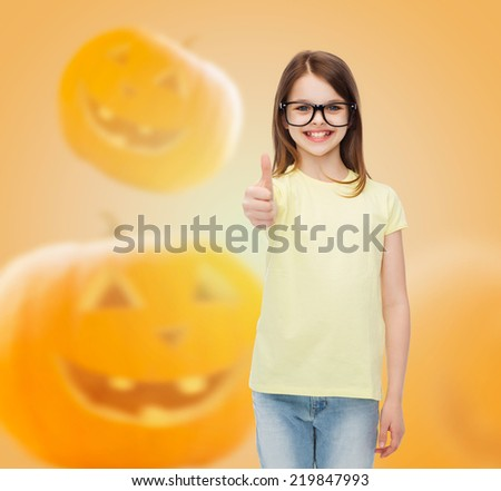 gesture, education, holidays and people concept - smiling little girl in glasses showing thumbs up over halloween pumpkins background - stock photo