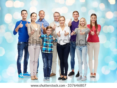 gesture, family, generation and people concept - group of smiling men, women and boy showing thumbs up over blue holidays lights background - stock photo