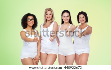 gesture, friendship, beauty, body positive and people concept - group of happy different women in white underwear showing thumbs up over green natural background - stock photo