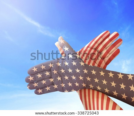 Gesture made by american flag colored hands showing symbol of eagle over blurred beautiful blue sky background. Concept for Independence Day and other events. - stock photo
