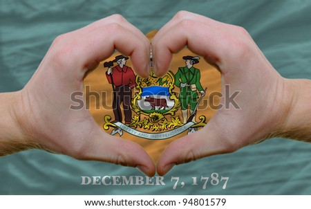 Gesture made by hands showing symbol of heart and love over us state flag of delaware - stock photo