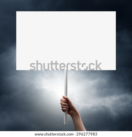 gesture of hand holding a blank white paper isolated over dramatic dark sky background - stock photo