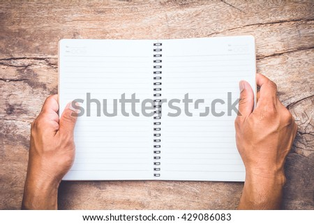 gesture of male's hand holding a notebook on old wooden table - stock photo