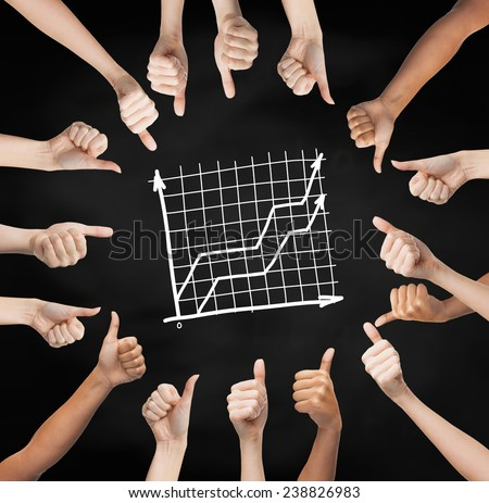 gesture, people, business and development concept - human hands showing thumbs up in circle over black board background with graph - stock photo