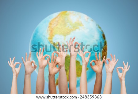 gesture, people, humanity and community concept - human hands showing ok sign over earth globe and blue background - stock photo